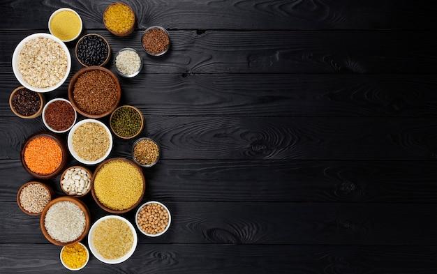 Cereais, grãos, sementes e grumos preto fundo de madeira