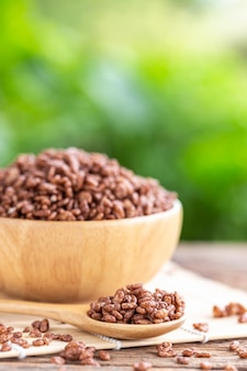 Cereais matinais, arroz com cacau na tigela na mesa de madeira com espaço verde borrão
