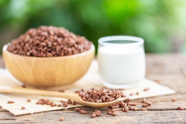 Cereais matinais, arroz tufado com cacau na tigela e copo de leite na mesa de madeira