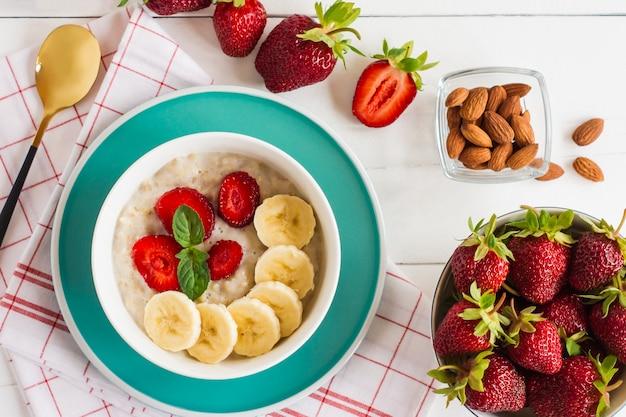 Cereais muesli de aveia em uma tigela com morango, banana e amêndoas. café da manhã saudável.