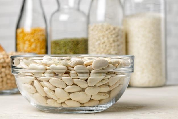 Cereais ou feijões crus nos frascos de vidro fecham-se acima. comida vegetariana e vegetariana. fechar-se.