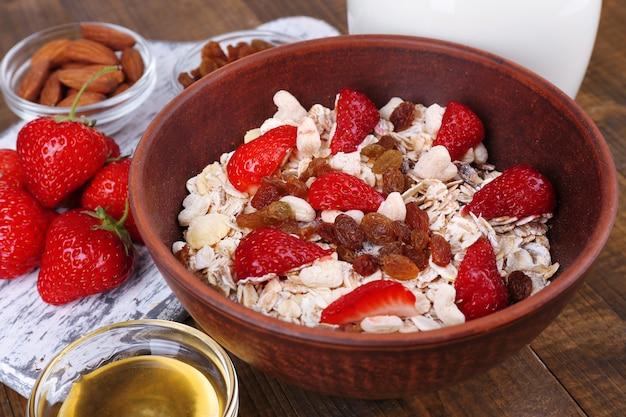 Cereais saudáveis com leite e morango na mesa de madeira