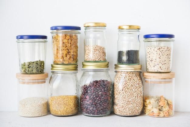 Cereais secos e sementes em potes de vidro, o conceito de nutrição saudável (feijão, quinua, sementes de abóbora, sementes de gergelim, passas, macarrão). desperdício zero