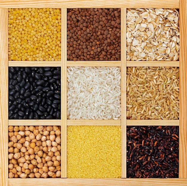 Cereais secos, grumos e feijões na vista superior da caixa de madeira