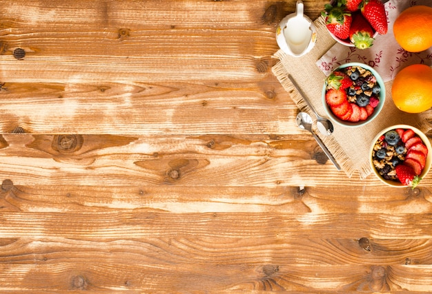 Cereal. café da manhã com muesli e frutas frescas em tigelas na madeira