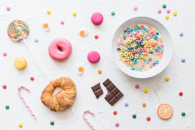 Cereal colorido na tigela de leite sobre o alimento doce no pano de fundo texturizado