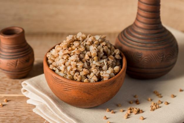 Cereal cozido trigo mourisco em tigela de barro marrom na mesa de madeira. grãos sem glúten para uma dieta saudável