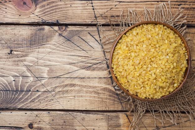 Cereal cru seco turco tradicional do bulgur em uma bacia de madeira.