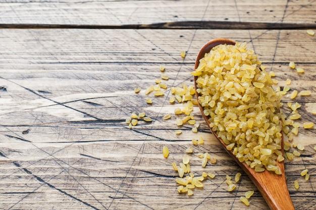 Cereal cru seco turco tradicional do bulgur em uma colher de madeira.