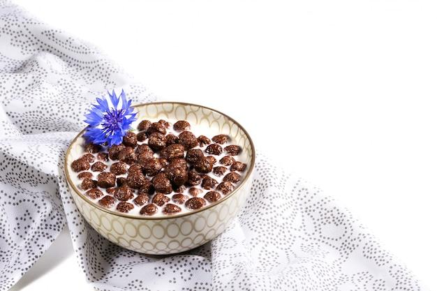 Cereal de café da manhã, cereais de chocolate no leite com flor de centáurea em um guardanapo branco, conceito de nutrição saudável para crianças antes da escola. copie o espaço