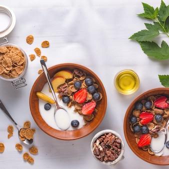 Cereal de placa de saúde com morangos e iogurte numa toalha de mesa branca