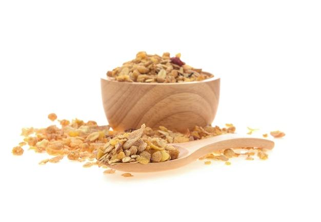 Cereal na colher e na bacia de madeira da madeira no fundo branco.