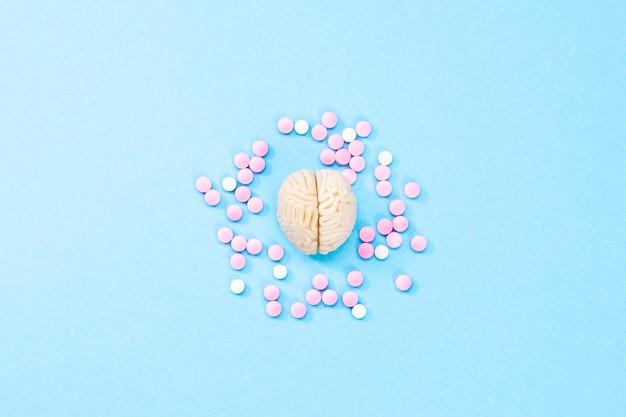 Cérebro com comprimidos brancos e rosa. algumas pílulas para o cérebro. simbólico para medicamentos, psicofármacos, nootrópicos e outros medicamentos. remédio. tratamento cerebral