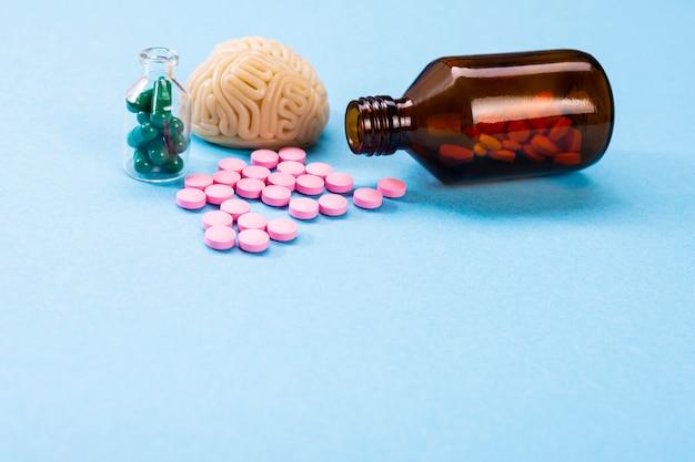 Cérebro com comprimidos cor de rosa e verdes em uma garrafa de vidro. simbólico para medicamentos, psicofármacos, nootrópicos e outros medicamentos. remédio. tratamento cerebral