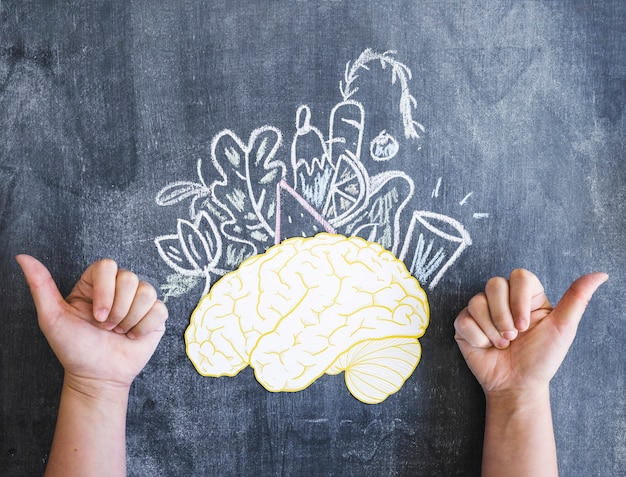 Cérebro e legumes desenhados com o polegar para cima o sinal na lousa