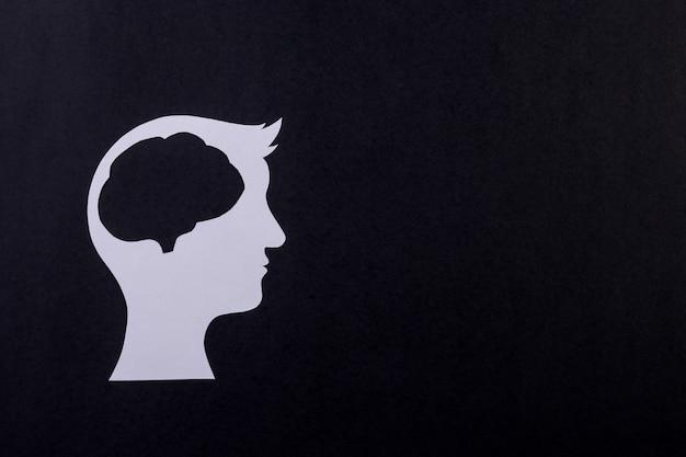 Cérebro humano feito de papel cortado em fundo preto. criatividade ou conceito de ideia inteligente.