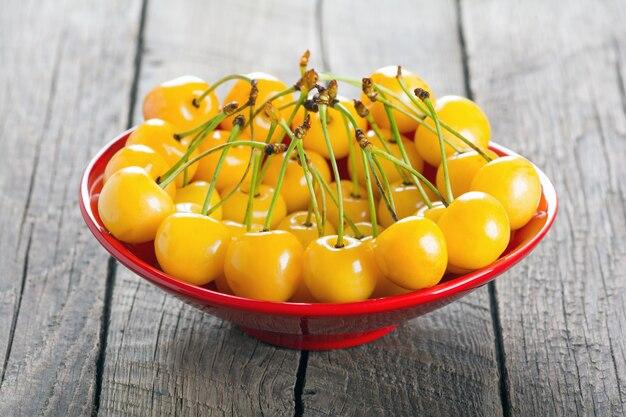Cereja amarela em uma tigela sobre um fundo de madeira