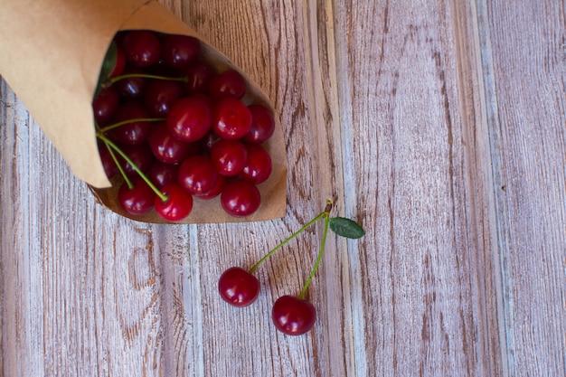 Cereja. cereja vermelha madura em um saco de papel em uma superfície de madeira velha.