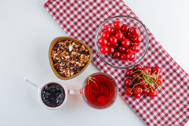Cereja com chá, geléia, ervas secas em uma tigela em branco e toalha de cozinha, plana leigos.