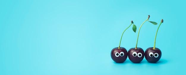 Cereja com olhos em um fundo azul. engraçado legumes e frutas para crianças. conceito de comida para bebé, comida cara.