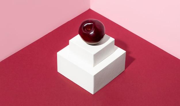 Cereja de ângulo alto com fundo rosa