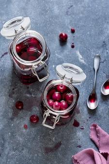 Cereja de maraschino em potes de vidro ingrediente alimentar plano