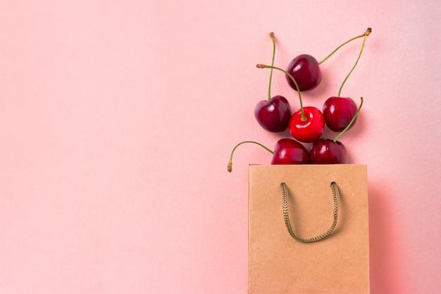 Cereja doce e saco de papel em rosa