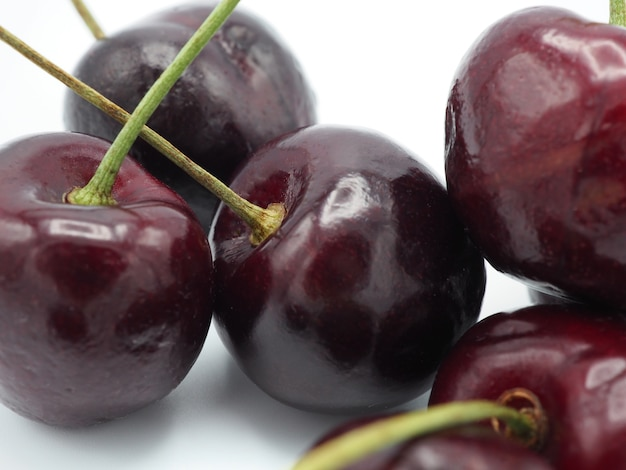 Cereja doce fresca no carrinho de compras ou no trole isolados no fundo branco.