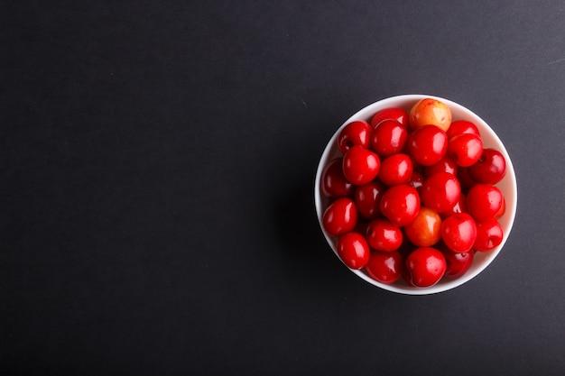 Cereja doce vermelha fresca na bacia branca. vista do topo.