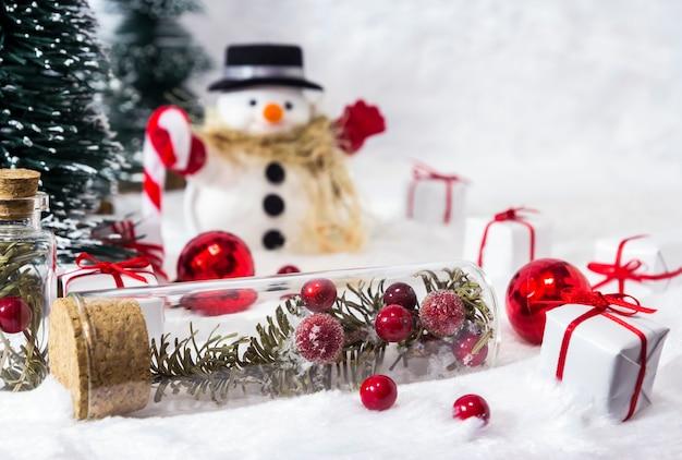 Cereja e folhas de pinheiro na garrafa de vidro na neve