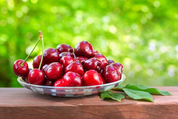 Cereja em uma bandeja de vidro nas hortaliças. dia de sol brilhante. frutas suculentas, saborosas e saudáveis.