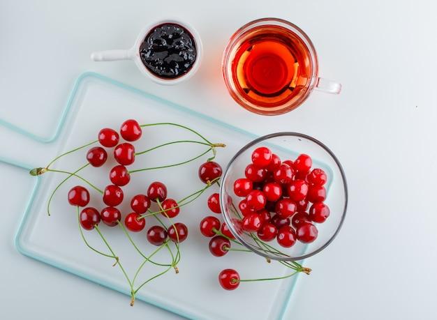 Cereja em uma tigela com chá, geléia plana colocar no branco e tábua