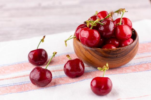 Cereja fresca na mesa de madeira branca. bagas maduras em gotas de água
