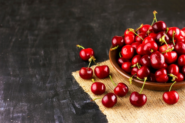 Cereja fresca na mesa de madeira preta. bagas maduras em gotas de água