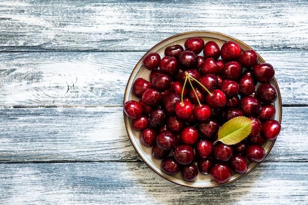 Cereja fresca na placa no fundo azul de madeira. cerejas maduras frescas. cerejas doces