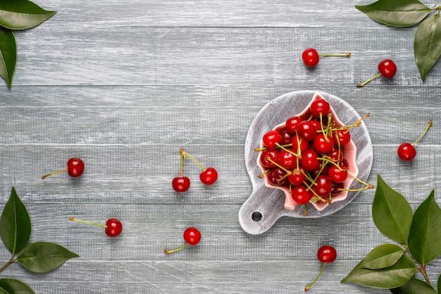 Cereja fresca no prato na vista superior de mesa cinza