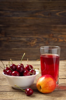 Cereja, maçã e um copo de suco em uma mesa de madeira