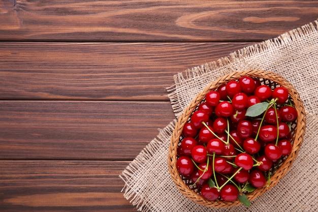 Cereja na cesta de madeira com folhas na mesa marrom.