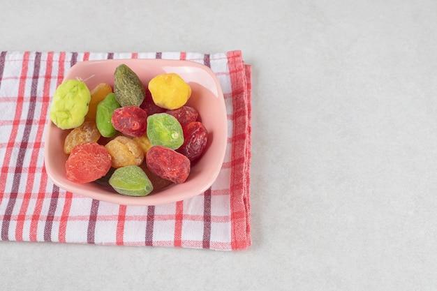 Cereja seca colorida e damascos em uma xícara de cerâmica.