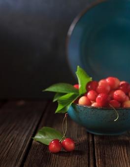 Cereja suculenta fresca em tigela sobre fundo de madeira vintage.