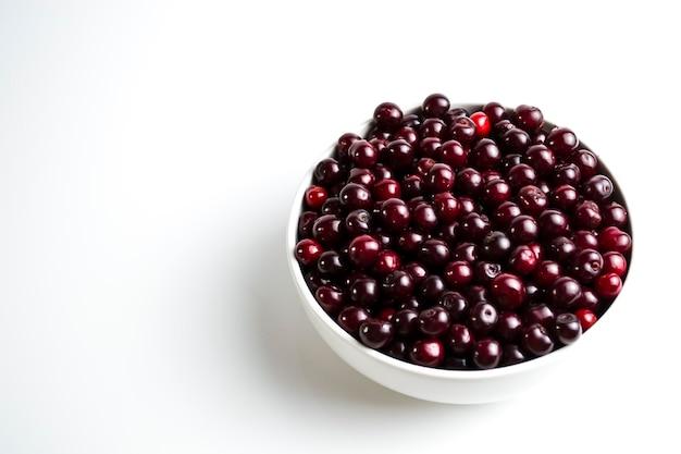 Cereja vermelha escura em uma xícara branca em um fundo branco