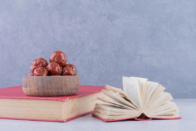 Cerejas ácidas marrons meio secas em uma xícara no fundo de concreto. foto de alta qualidade