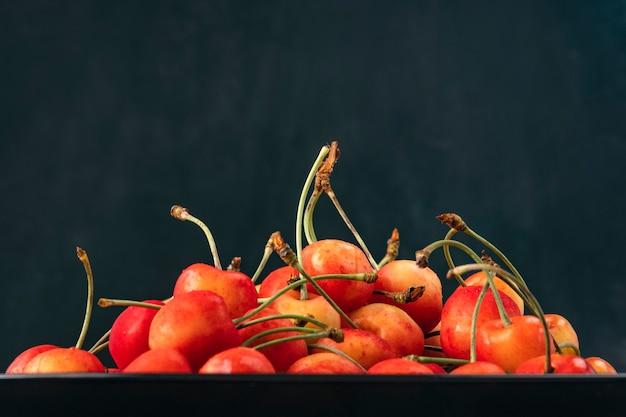Cerejas amarelo-vermelhas em uma bandeja em fundo preto. cerejas maduras e suculentas. frutas apetitosas sazonais.