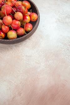 Cerejas as apetitosas cerejas amarelo-avermelhadas na mesa cinza-creme