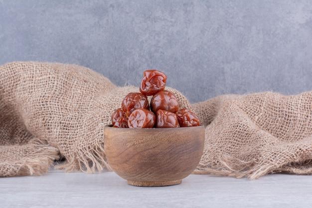 Cerejas azedas marrons meio secas em uma xícara na superfície de concreto