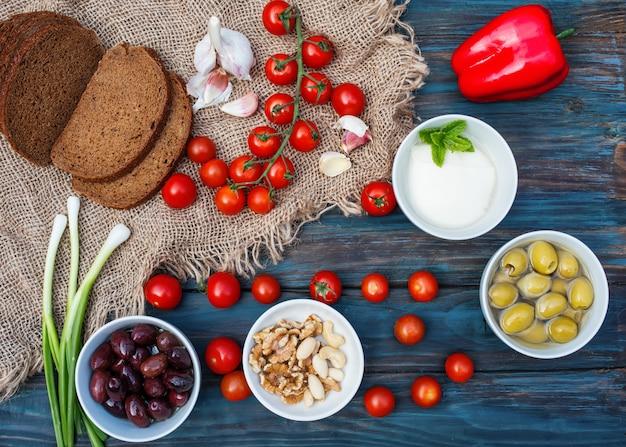 Cerejas, cebolinhas, coentro, queijo, alho, azeitonas em uma tigela, pão, pimentão no fundo escuro de madeira rústico