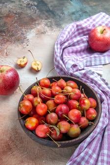Cerejas cerejas na tigela maçãs na toalha de mesa quadriculada