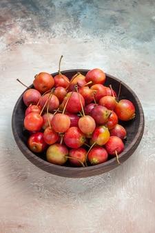 Cerejas cerejas vermelho-amarelas na tigela de madeira em cima da mesa