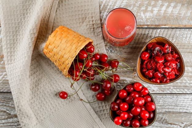 Cerejas com coquetel, geléia na tigela e cesta na toalha de madeira e cozinha