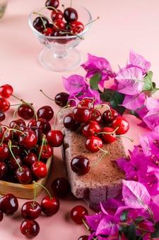 Cerejas com flores, tijolo na placa de madeira e vaso na superfície rosa